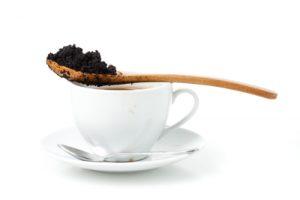 En sked med kaffesump ligger över en vit kaffekopp