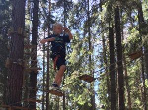 Pojke balanserar på höghöjdsbana